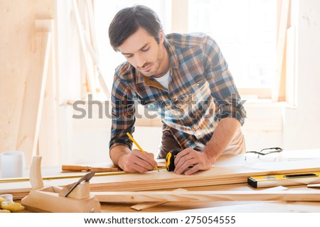 Precision throughout. Serious young male carpenter working with wood in his workshop