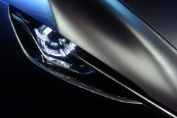 Predatory car headlight and hood of powerful sports grey car with blue glare on dark background