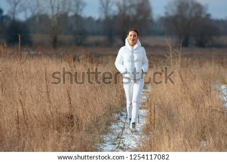 Preety smiling girl dressed all in white walks through the high dry grass field by snowy pathway at winter countryside