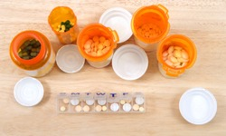 Prefilling once a day medication box with many pills. The importance of medication management cannot be overstated, especially when it comes to the care of seniors. Med boxes assist with management.