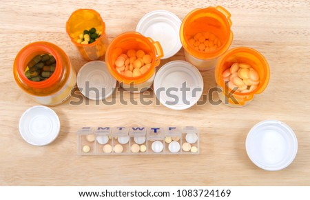Prefilling once a day medication box with many pills. The importance of medication management cannot be overstated, especially when it comes to the care of seniors. Med boxes assist with management. #1083724169
