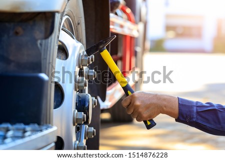 Preforming a pre-trip inspection on a truck,Concept preventive maintenance truck checklist,Truck driver holding hammer with checking of truck wheels and tires,spot focus. Imagine de stoc ©