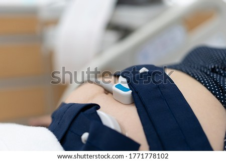 Pregnancy care. Fetal heartbeat monitoring by cardiotocography from electronic fetal monitor. Pregnant belly installed with belt for heartbeat examination. Pregnancy care technology concept. Stock photo ©