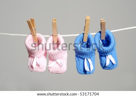 pregnancy concept: pink & blue baby booties hanging on a clothes line
