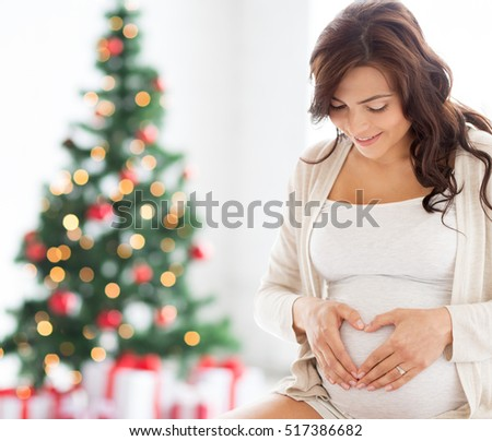 pregnancy, love, holidays, people and expectation concept - happy pregnant woman making heart gesture at home over christmas tree background