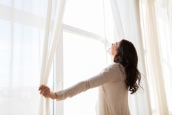 pregnancy, motherhood, people and expectation concept - close up of happy pregnant woman opening window curtains
