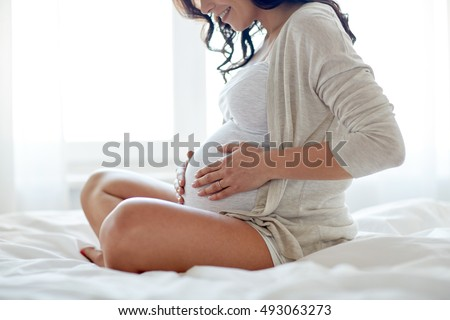 pregnancy, rest, people and expectation concept - close up of happy smiling pregnant woman sitting in bed and touching her belly at home