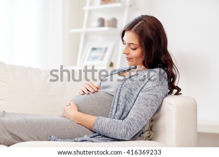 pregnancy, rest, people and expectation concept - happy pregnant woman lying on sofa at home