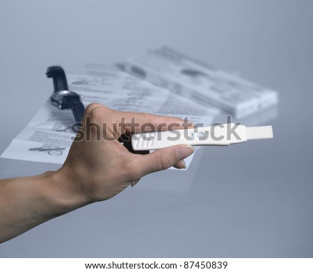 pregnancy test with hand and wristwatch in grey back