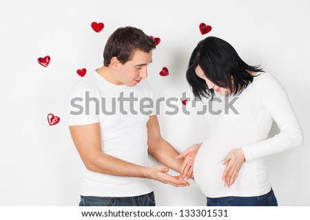 Pregnancy young woman with man in studio