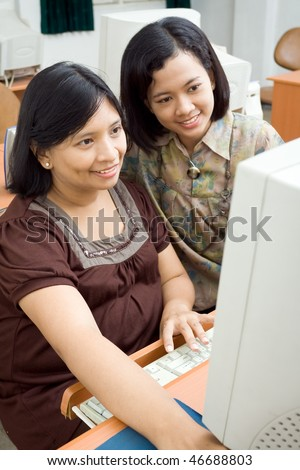 pregnant asian woman and friend enjoy browsing the internet at the office