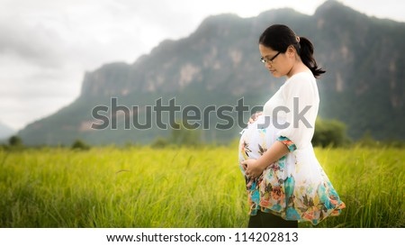 pregnant Asian woman wearing floral white dress affectionately holding her belly outside with newly planted rice field, mountains, and cloudy sky in background.