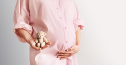 Pregnant belly of expectant mother with cute tiny teddy toy bear. Beautiful pregnant woman in pink shirt dress in white background. Loving mother waiting for baby birth. Pregnancy, gynecology concept.