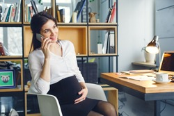 Pregnant business woman working at office motherhood sitting phone call