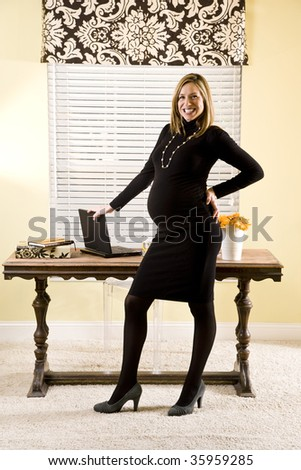 Pregnant businesswoman posing by her home desk