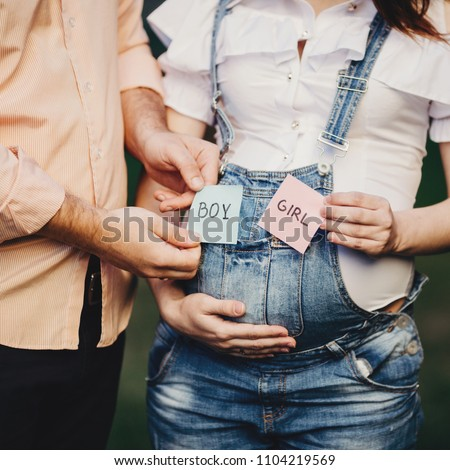 Pregnant couple expecting a baby.  Man and woman hands with BOY and GIRL cards near belly.  Pregnancy, maternity, family, motherhood, fatherhood, gender concept