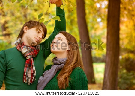 pregnant couple have fun in the park, throwing leaves