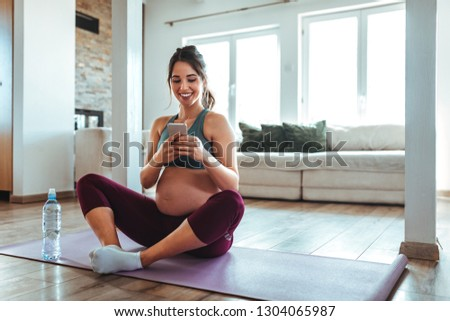 Pregnant female doing yoga at home and using cellphone #1304065987