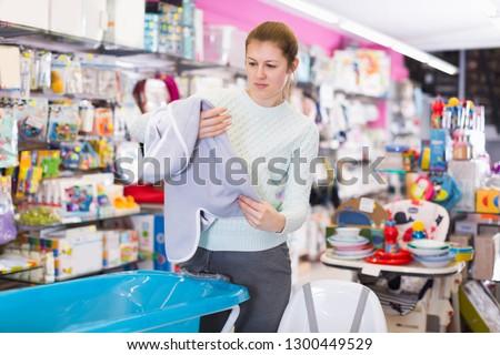 Pregnant  female is choosing baby towel in the shop.