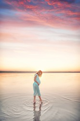 Pregnant girl in a dress at sunset walks on water