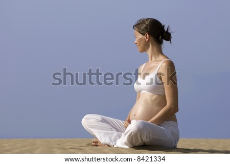 Pregnant girl on the beach on the dunes in Maspalomas in Gran Canaria