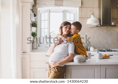 Pregnant mom with kid playing together and huging in the kitchen. Mother with son sharing good emotions while having breakfast at home.