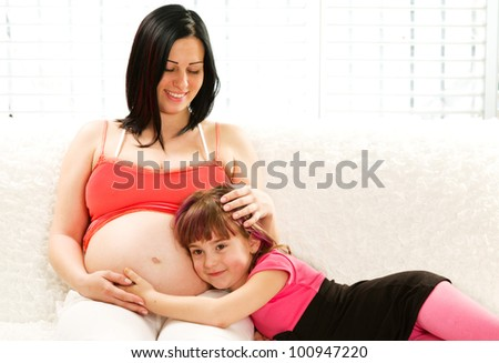 Pregnant mother and daughter sitting together