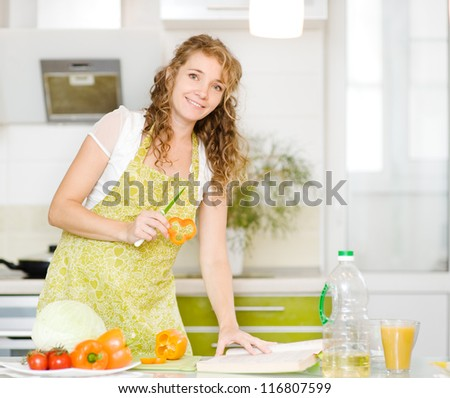 pregnant mother making healthy food standing happy smiling in kitchen. looking at camera.