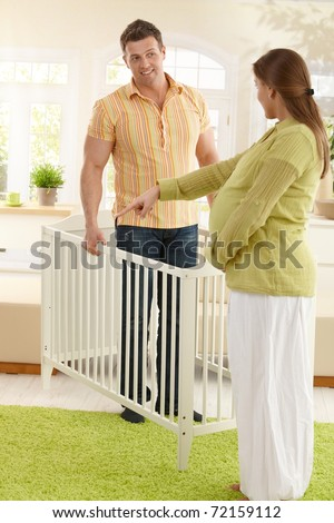 Pregnant mother pointing at right place of baby bed in living room, smiling father holding bed.?