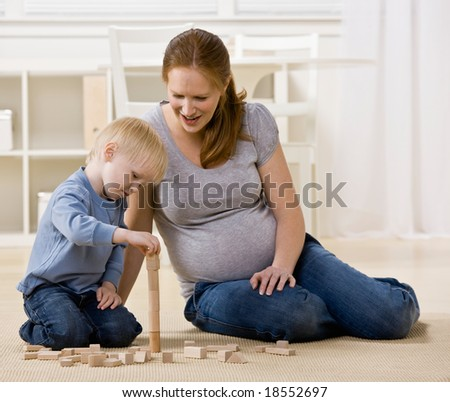 Pregnant mother proudly watches son stack wooden blocks