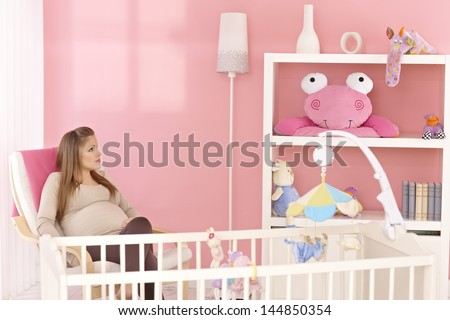 Pregnant mother sitting in armchair in pink baby's room, thinking.