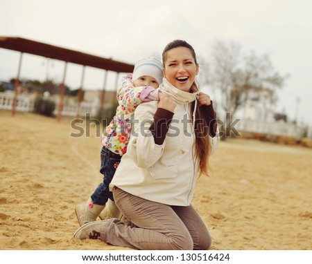 pregnant mother with baby daughter having fun on beach