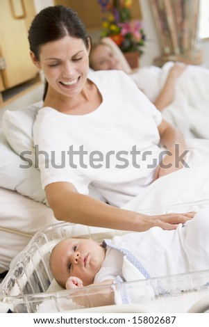 Pregnant mother with baby in hospital smiling