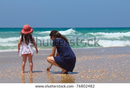 Pregnant mother with daughter  collecting shells on the beach