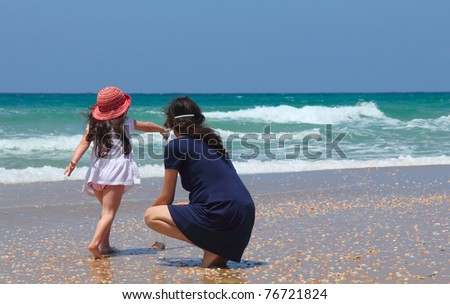 Pregnant mother with daughter on the beach - stock photo