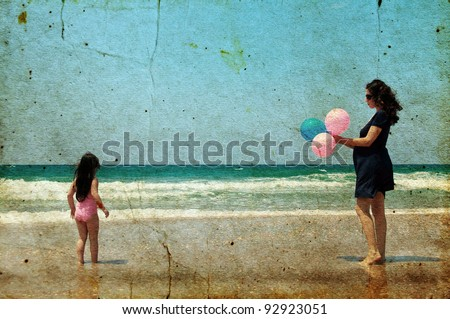 Pregnant mother with daughter on the beach with balloons - stock photo