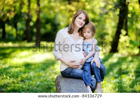 Pregnant mother with her small daughter outdoors
