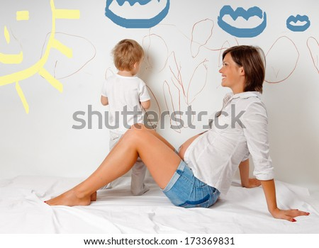 pregnant mother with her son on white bed. Child draws on the wall