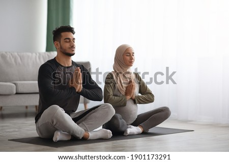 Pregnant Muslim Woman In Hijab Meditating Together With Her Husband At Home. Arab Couple Practicing Prenatal Yoga In Living Room, Sitting With Clasped Hands, Enjoying Healthy Lifestyle, Copy Space