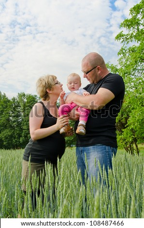 Pregnant parents with their one year old baby girl