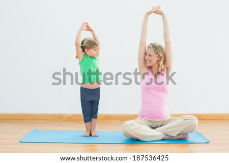 Pregnant smiling mother and daughter doing yoga together in a fitness studio - stock photo