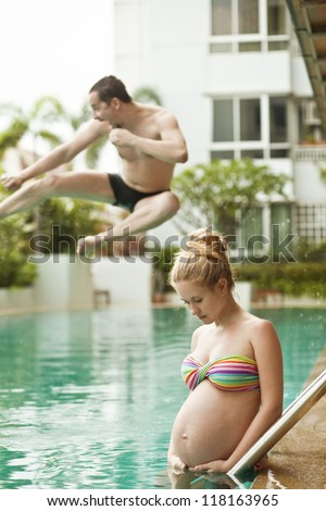 Pregnant woman against her husband jumping into the pool