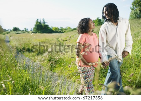 Pregnant woman and a man walking in a park