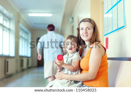 pregnant woman and child  with urinalysis sample at the clinic