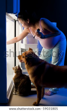 Pregnant woman and her pets looking for food in the refrigerator