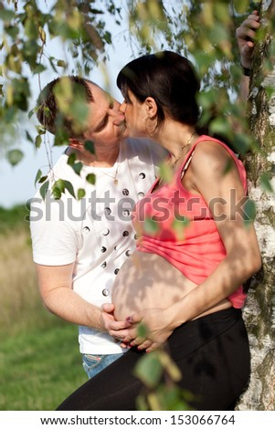 pregnant woman and man in the park. Kiss