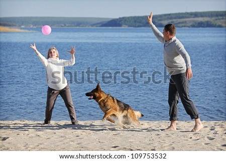 Pregnant woman and man playing with german sheep-dog