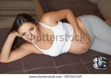 Pregnant woman at home lying on the sofa. Baby shoes.
