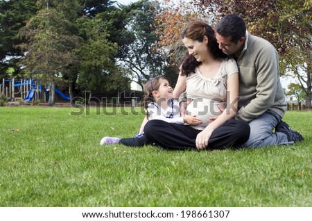 Pregnant woman been hug by her husband and daughter during pregnancy outdoor at the park. Concept photo of women healthy life style and health care. copyspace