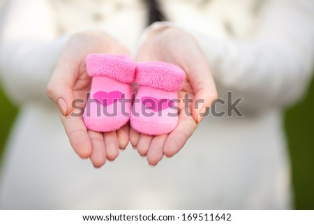Pregnant woman belly holding pink baby booties, expecting girl. Healthy pregnancy.  - stock photo